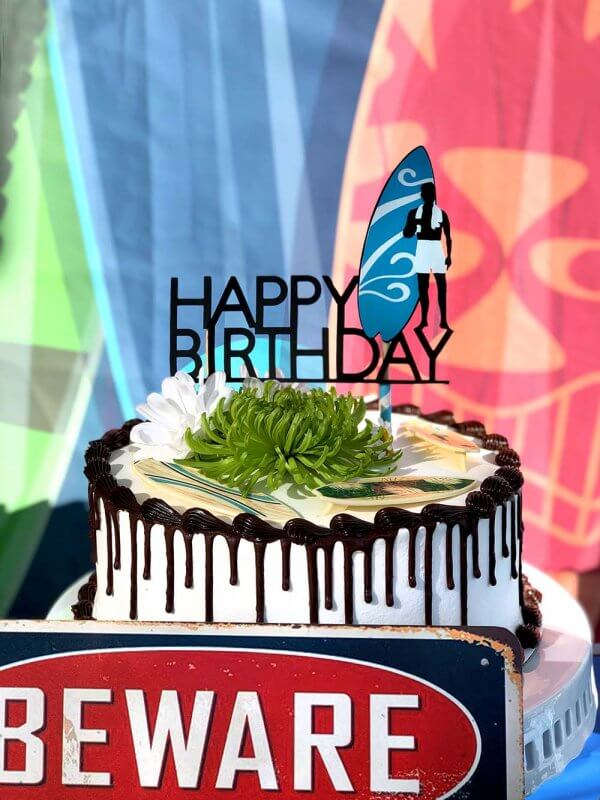 White birthday cake with chocolate drip and surf themed party topper