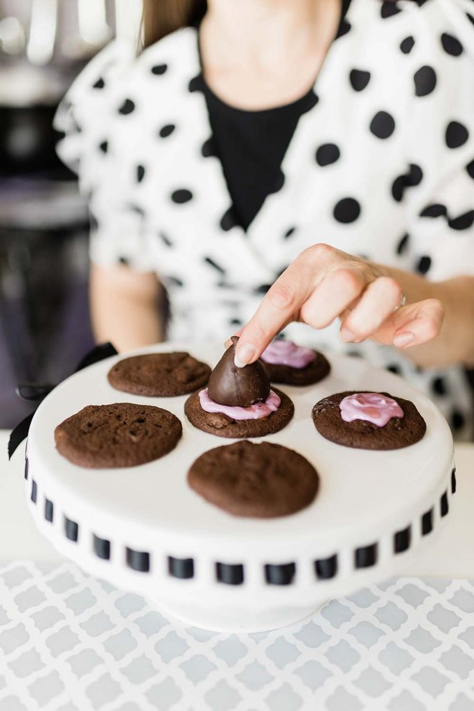 Placing chocolate covered strawberry onto purple chocolate cookie
