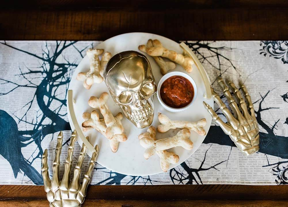 Bone Breadsticks on tray with gold skull on table
