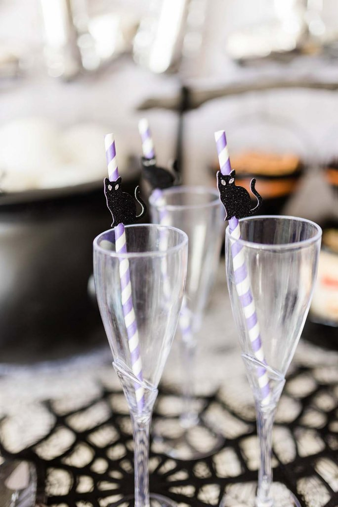 Plastic drink flutes with purple striped paper straws and black cat
