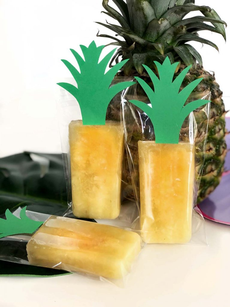 Packaged pineapple popsicles with green paper stems