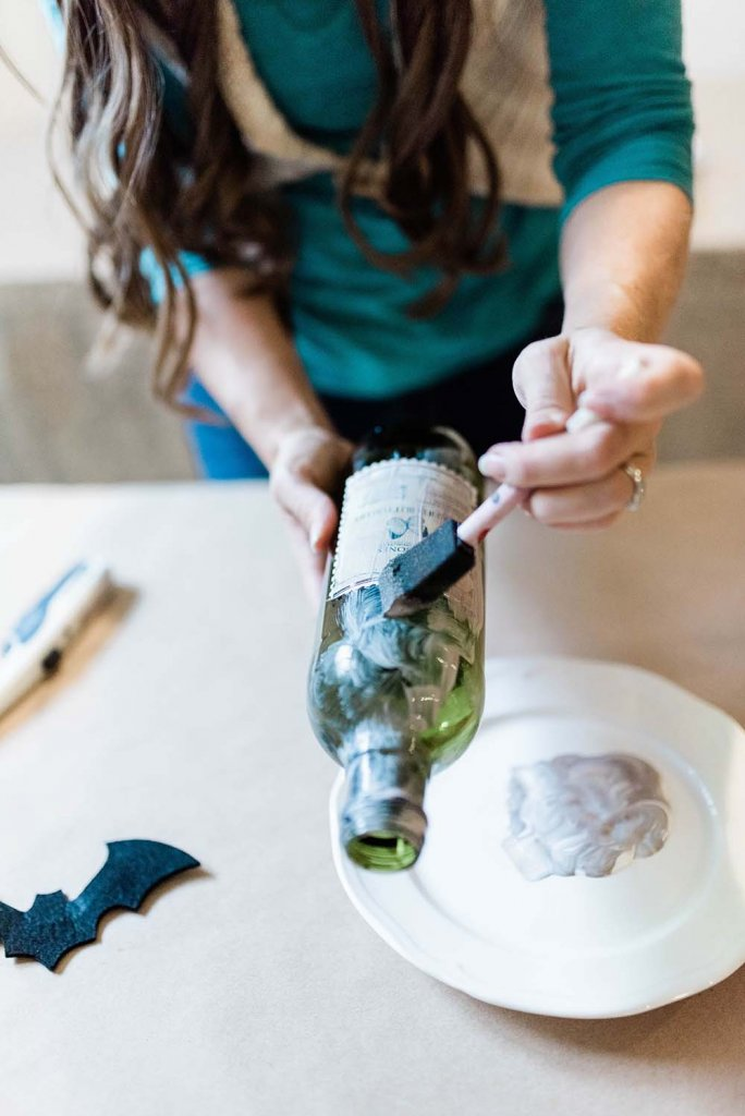 Distressing green bottle with paint for diy apothecary jars