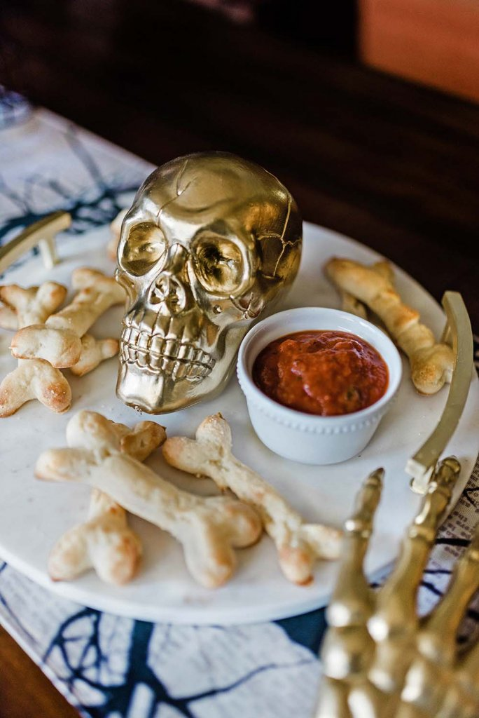 Bone breadsticks and marinara on tray with skull - finger food for halloween