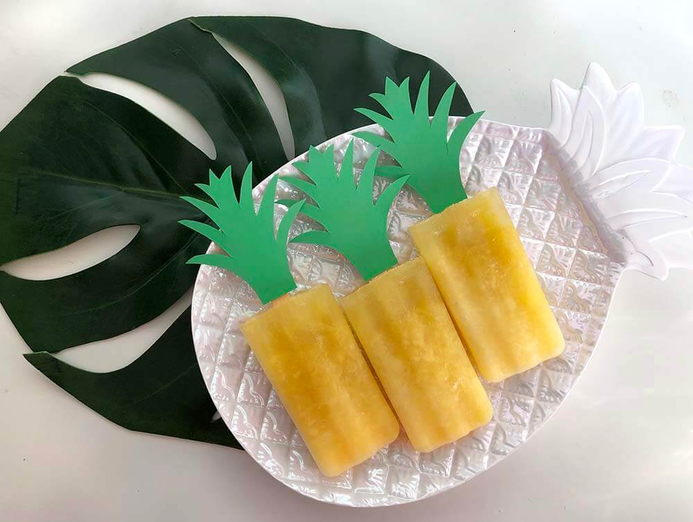 Pineapple popsicles on plate with paper stems
