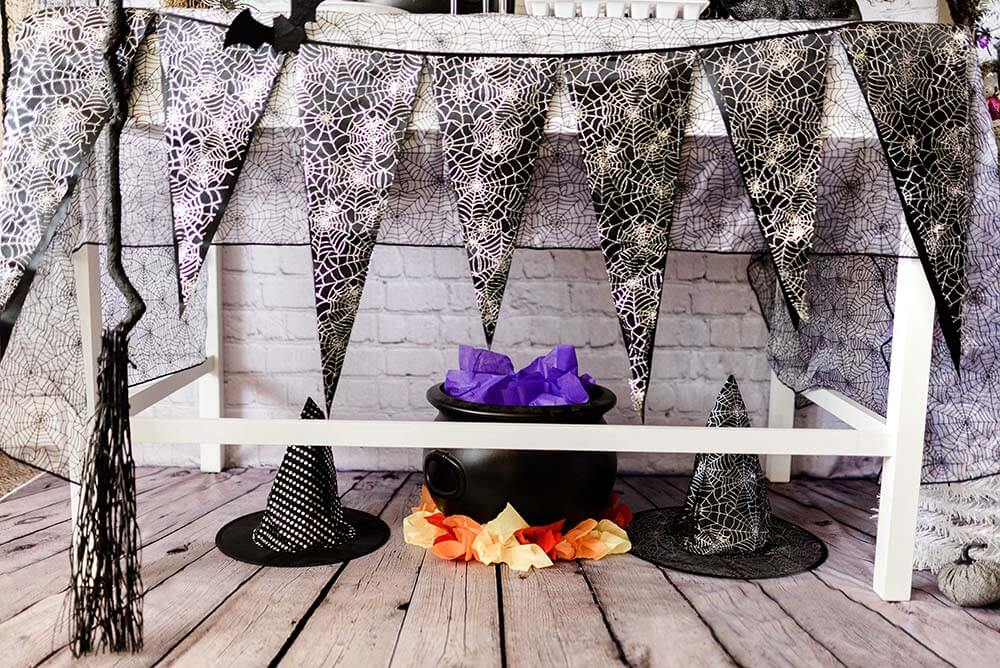 Cauldron and witch hats under table display