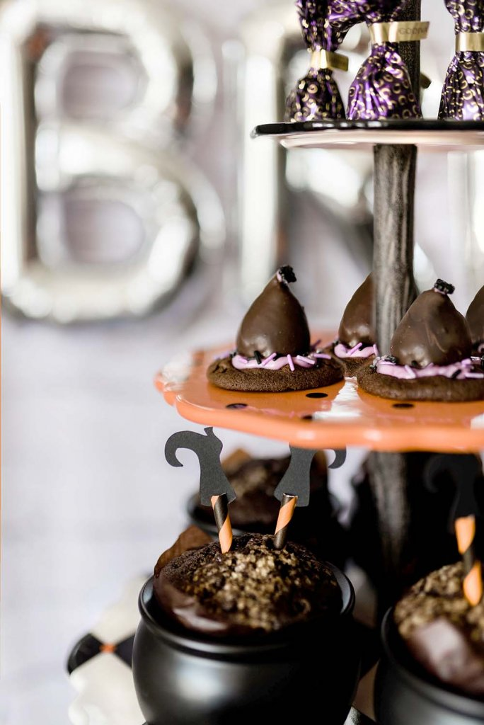 Chocolate witch brooms, witch hat cookies, and cupcake cauldrons on stand