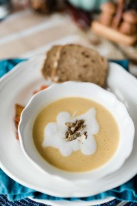 Butternut squash soup topped with coconut cream drizzle and roasted pumpkin seeds