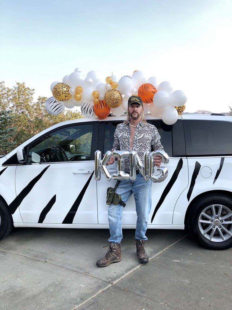 Minivan dressed up like white tiger with tiger king for Halloween car parade