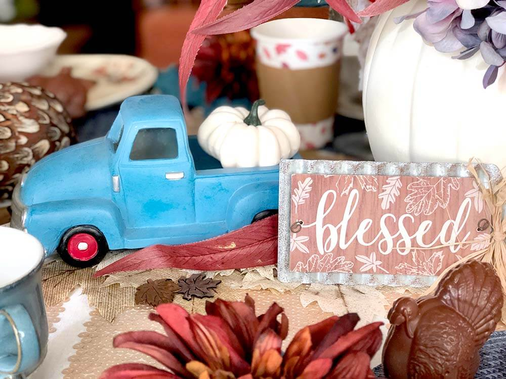 Rustic blue truck with pumpkin and blessed tag on table