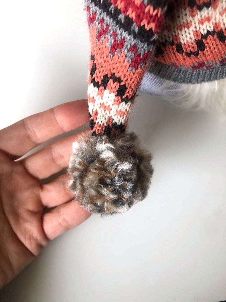 Handmade pom at end of sweater gnome hat
