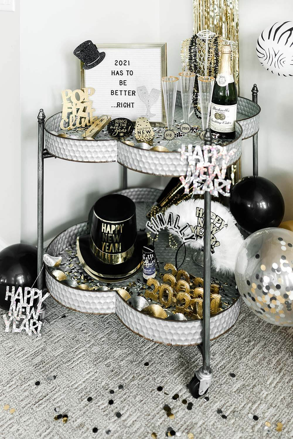 Bar cart with non-alcoholic bubbly, noise makers, and accessories for New Years Eve Party