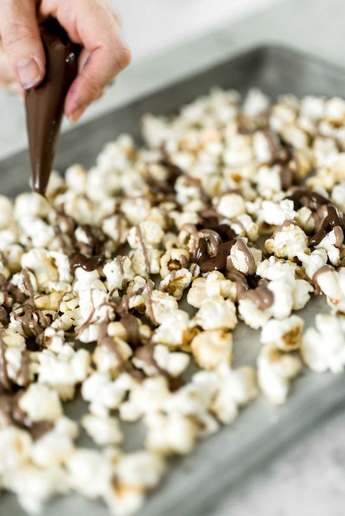 Drizzling dark chocolate over popcorn for party