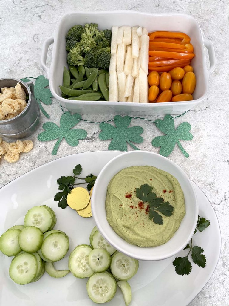 Veggies and green avocado hummus for St Patrick's Day food celebration