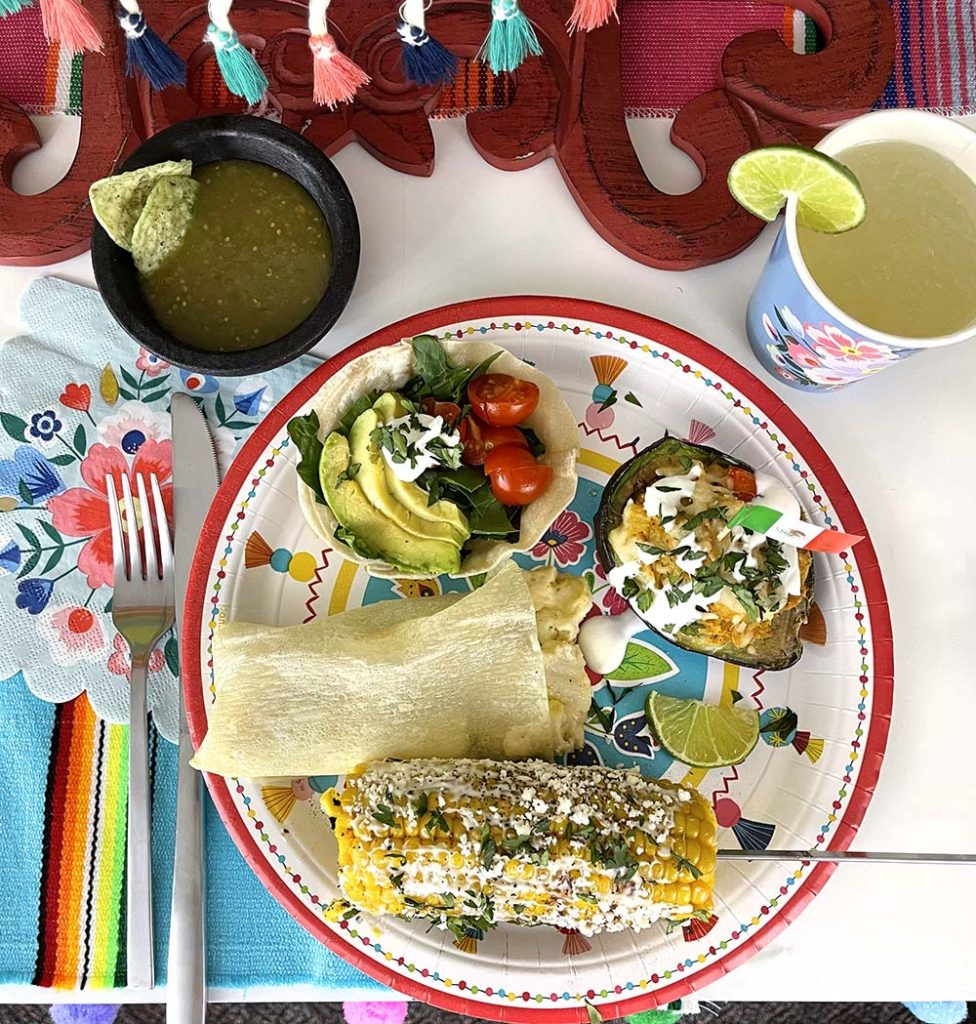 Fiesta dinner with grilled corn, tamales, stuffed avocado, and tostada