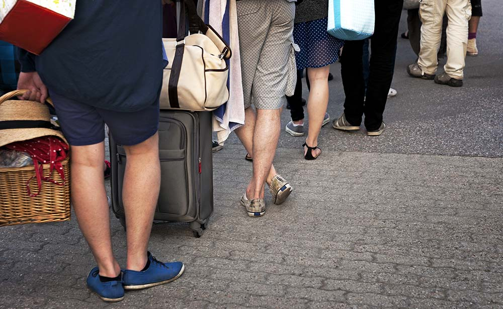 Feet of people with luggage in casual clothes waiting patiently in line