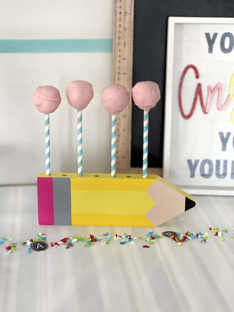 dipped chocolate date balls drying on pencil stand for back to school party