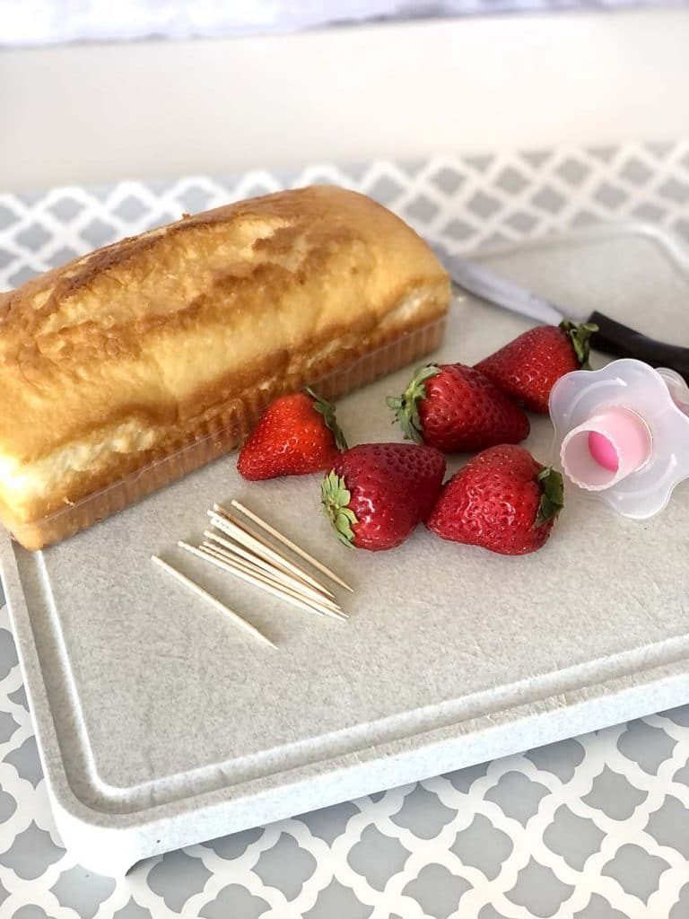 Angel food cake and strawberries on cutting board