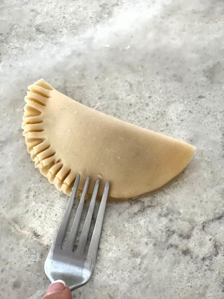Crimping the edges of a pumpkin pasty hand pie