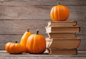 Stack of books with pumpkins on a table
